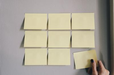 Hand taking a post it note